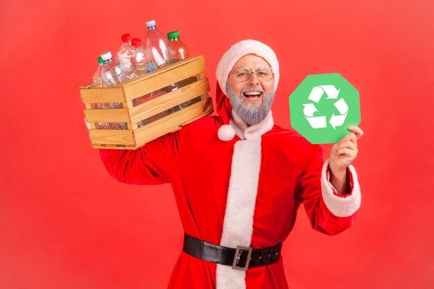 Papai noel segurando uma caixa com garrafas de plástico no ombro e mostrando o sinal de reciclagem.