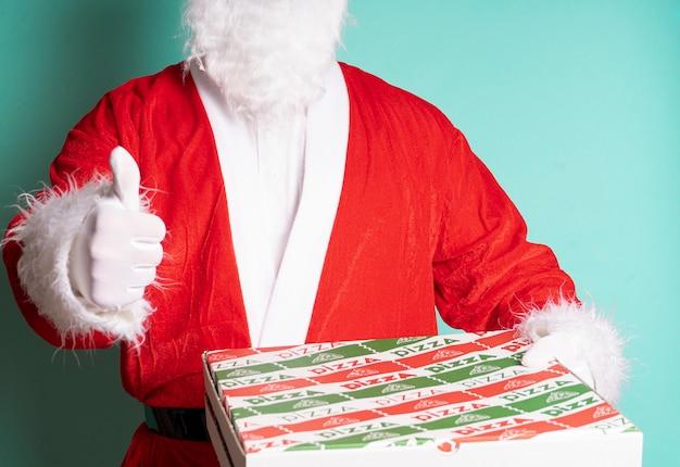 Papai noel segurando uma caixa de pizza e fazendo sinal de positivo isolado em azul