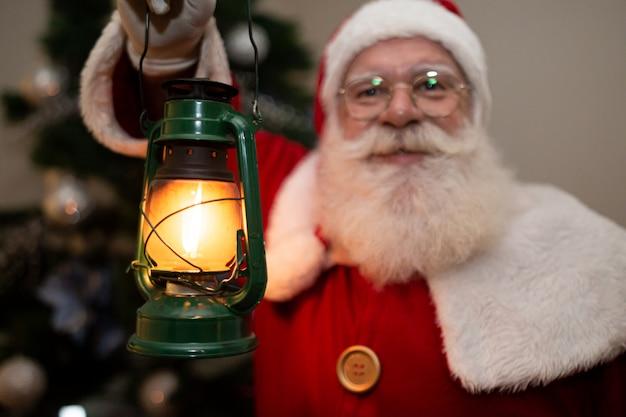 Papai noel segurando uma lâmpada silenciosa em uma casa