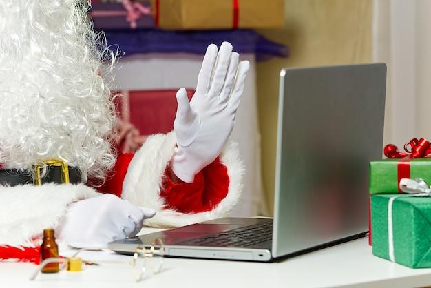 Papai noel sentado atrás do laptop. papai noel em um confinamento sentado atrás de um laptop conduz online