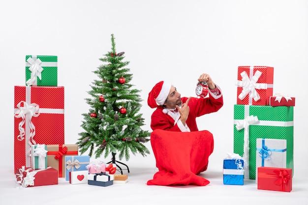 Papai noel sentado com caixas de presente e uma árvore
