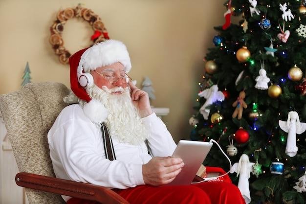 Papai noel sentado com um tablet digital em uma cadeira confortável perto da árvore de natal em casa