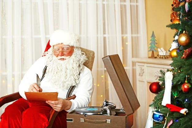Papai noel sentado com uma lista de desejos de crianças em uma cadeira confortável perto da lareira em casa
