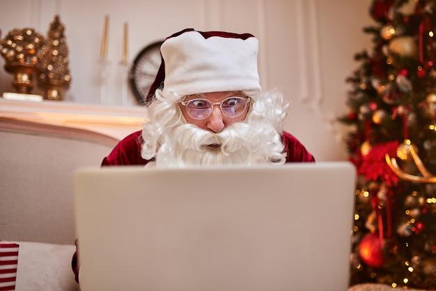 Papai noel sentado em sua casa e lendo e-mail no laptop com o pedido de natal ou lista de desejos perto da lareira e árvore com presentes. feliz natal, conceito de boas festas