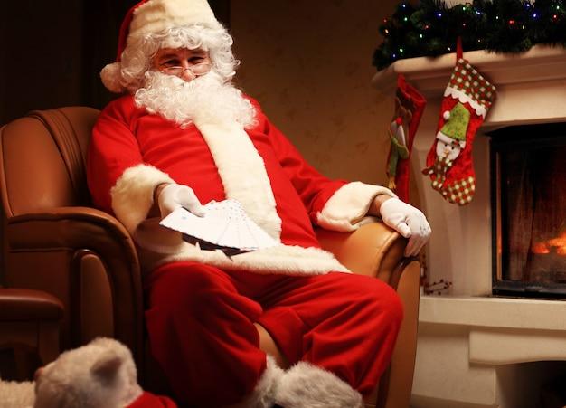 Papai noel sentado na árvore de natal, segurando cartas de natal e descansando junto à lareira. decoração de casa