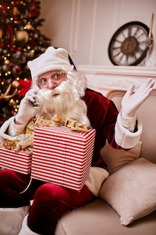 Papai noel sentado no sofá e falando no celular perto da lareira e a árvore de natal com presentes. ano novo e feliz natal, conceito de boas festas