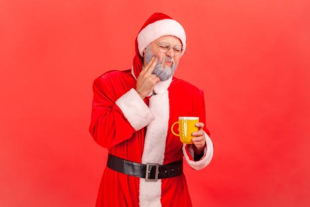 Papai noel sofrendo de terríveis dores nos dentes depois de beber uma bebida quente ou fria.