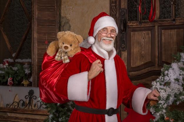 Papai noel sorridente segurando uma sacola com presentes