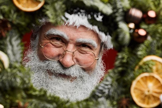 Papai noel sorrindo através de guirlanda de natal