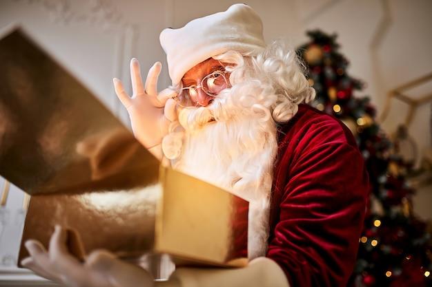 Papai noel surpreso com um presente mágico e brilhante perto da bela árvore de natal.