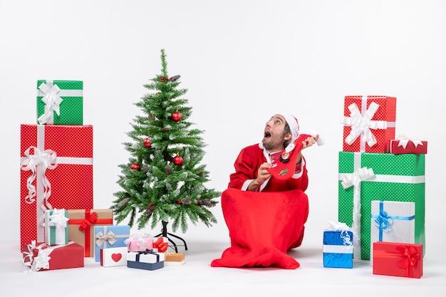 Papai noel surpreso, sentado no chão e segurando uma meia de natal, olhando para cima, perto de presentes, e decorado com árvore de ano novo em fundo branco