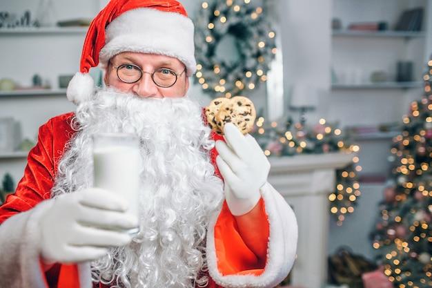 Papai noel tem copo de leite e dois biscoitos nas mãos. ele oferece.