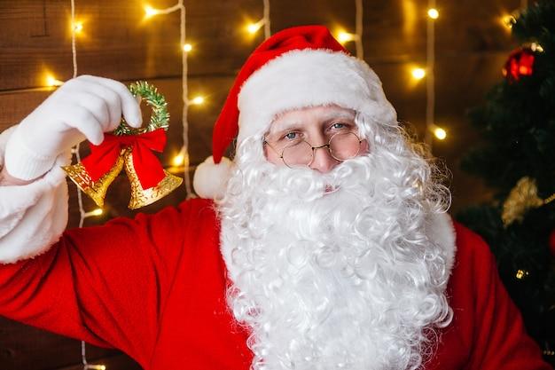 Papai noel tocando um sino perto de árvore de natal com presentes