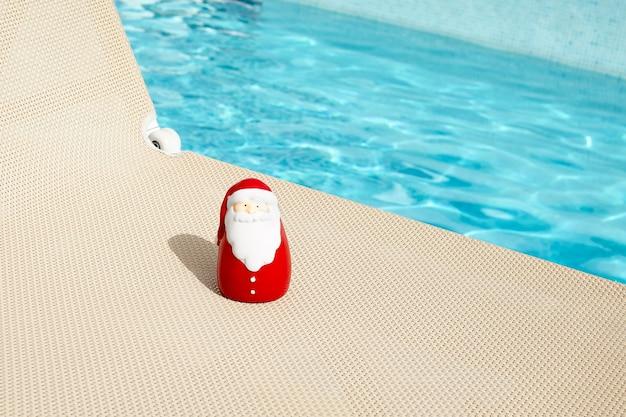 Papai noel toma banho de sol em um resort.