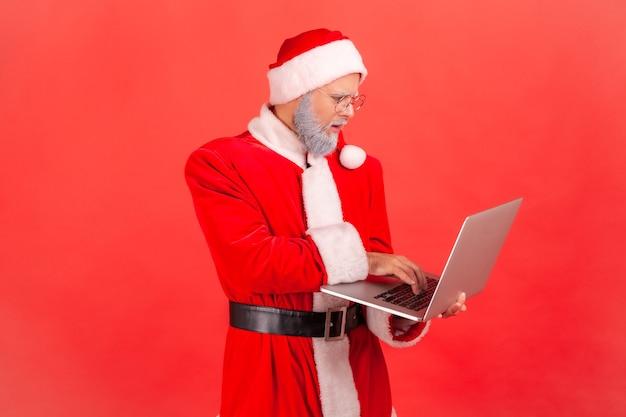 Papai noel trabalhando no laptop, pensando no novo projeto.
