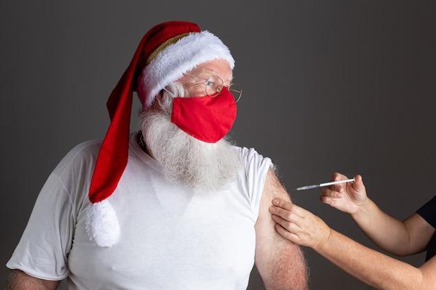 Papai noel usando máscara facial sendo vacinado com injeção
