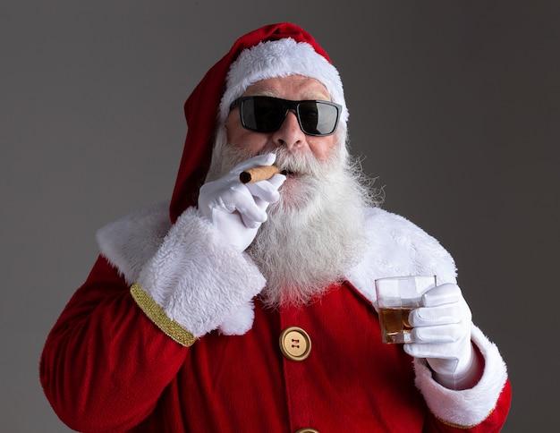 Papai noel usando óculos escuros, fumando um charuto e bebendo batedor em fundo escuro