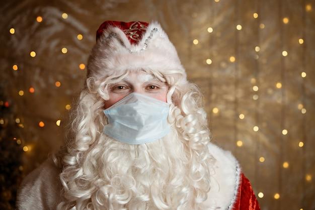 Papai noel usando uma máscara médica no fundo de uma parede com bokeh de guirlandas