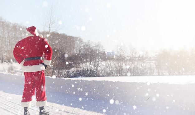 Papai noel vem com presentes do exterior. papai noel em um terno vermelho com barba e usando óculos está caminhando ao longo da estrada para o natal. o pai natal traz presentes para as crianças.