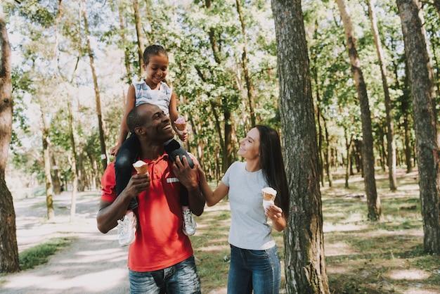 Papai rola uma garotinha em volta do pescoço na floresta.