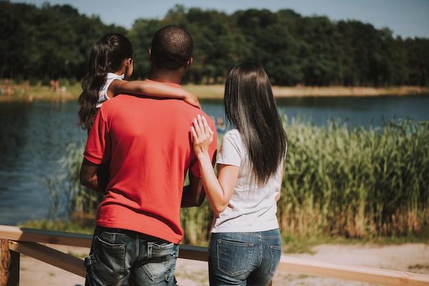 Papai segura a menina nos braços e olha para o outro lado.
