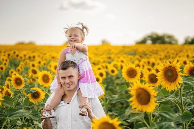 Papai segura nos ombros uma filhinha. a garota aponta para algo com o dedo. campo de girassol. pôr do sol