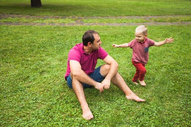 Papai sentou na grama e brincou com seu filho no parque