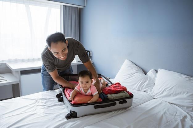 Papai sorri segurando um bebê fofo deitado em uma mala aberta
