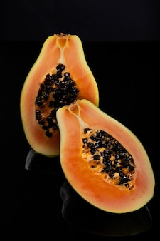 Papaia em fatias na superfície brilhante preta