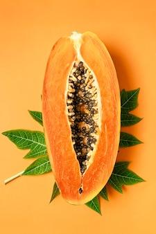 Papaias maduras recém-cortadas com folhas verdes em laranja