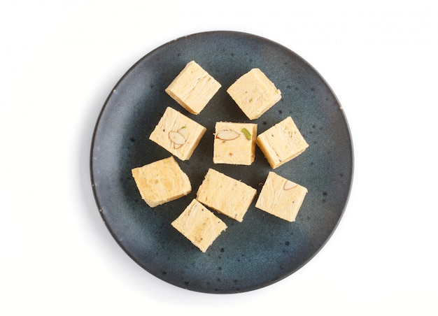 Papdi indiano tradicional do soan dos doces na placa cerâmica azul isolada em um fundo branco