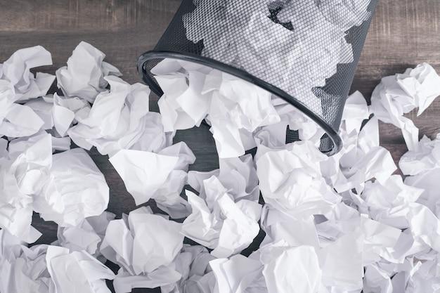 Papéis amassados na lata de lixo.
