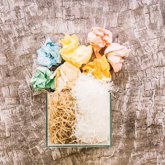 Papéis amassados sobre o recipiente de vidro preenchido com woodhave e plasticshave