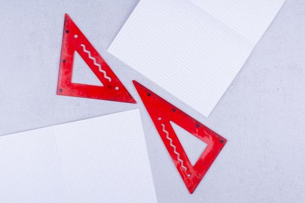 Papéis brancos em branco com réguas vermelhas no chão