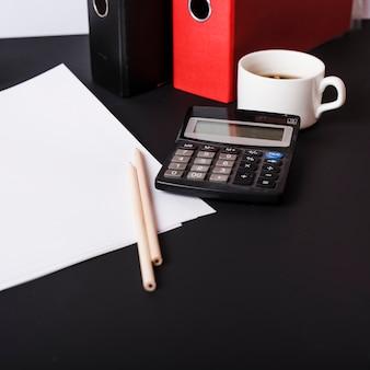 Papéis brancos em branco; lápis; arquivos em papel; xícara de café e calculadora na mesa preta