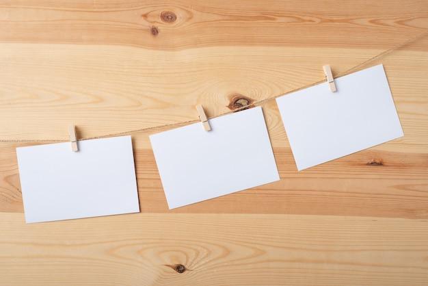 Papéis brancos em branco na corda contra uma madeira