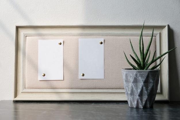 Papéis brancos em branco na moldura de madeira vintage marrom pendurada na parede de mármore preto e branco