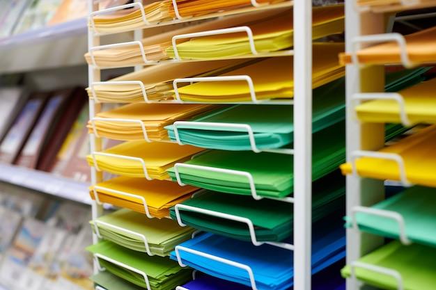 Papéis de arte coloridos expostos na prateleira de uma papelaria