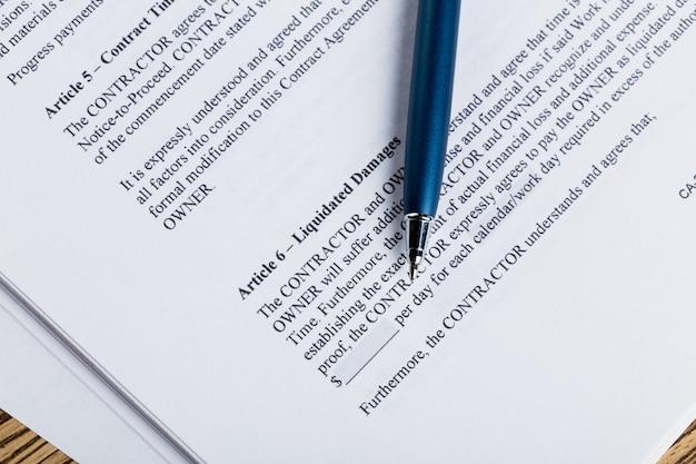 Papéis de caneta e contrato na mesa de madeira