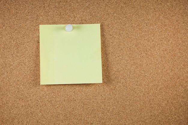 Papéis de nota amarela sobre fundo de placa de cortiça.