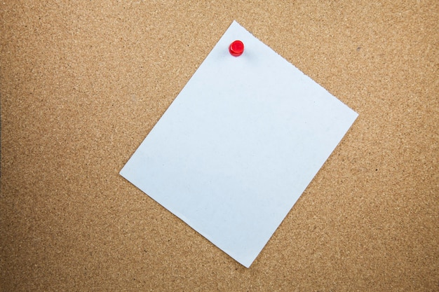 Papéis de nota branca sobre fundo de placa de cortiça.