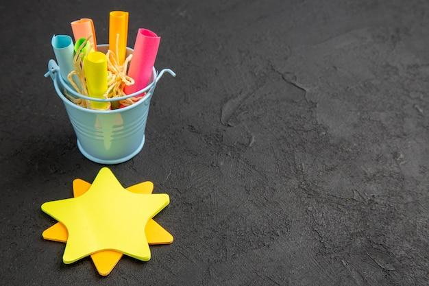 Papéis de nota de estrela de vista inferior enrolados em notas auto-adesivas amarradas com corda em um pequeno balde na mesa preta