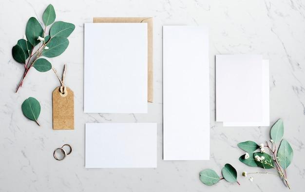Papéis em branco, deitado na mesa de mármore com decoração de folhas