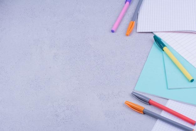 Papéis em branco e lápis coloridos na superfície cinza