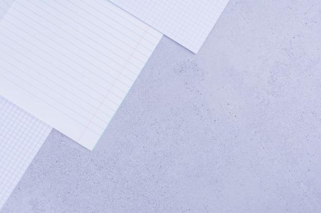 Papéis em branco isolados em cinza.