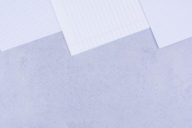 Papéis em branco isolados em superfície cinza