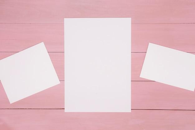 Papéis em superfície de madeira rosa