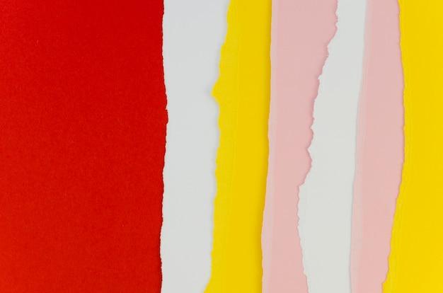 Papéis rasgados verticais vermelhos e amarelos