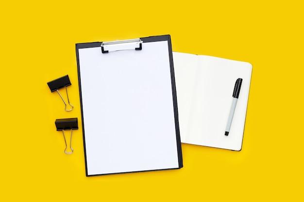 Papel a4 em branco na área de transferência preta, clipes de papel de escritório pretos com caderno e caneta em fundo amarelo.