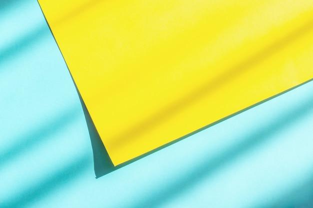 Papel abstrato azul e amarelo com luz e sombra dura